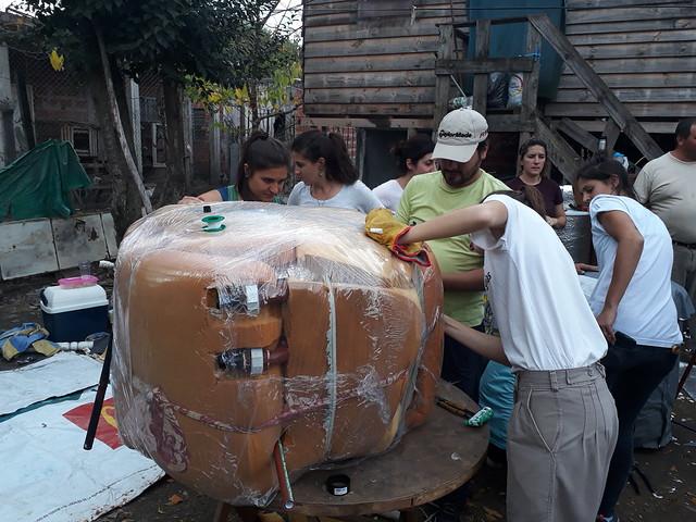 En el barrio pobre de Pinazo, en la periferia de la capital argentina, algunos jóvenes se afanan en recubrir un tanque térmico con capacidad para almacenar 90 litros de agua, con una capa de espuma reciclada de colchones viejos, que ayuda a mantener la temperatura del líquido calentado por un colector solar, también realizado con botellas plásticas y latas reutilizadas. Crédito: Daniel Gutman/IPS
