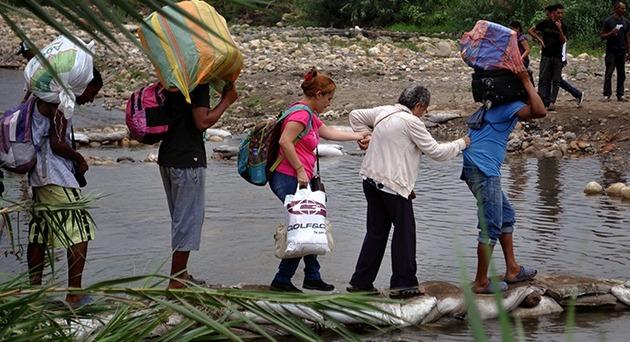 Un grupo familiar cruza el río Táchira, para ingresar desde Venezuela a Colombia. Crédito: Tomer Urwicz/UNFPA