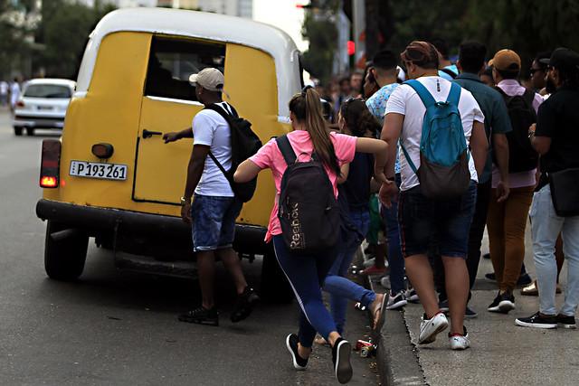 """Varios pasajeros abordan un """"taxi rutero"""", en las inmediaciones de la popular heladería Coppelia, en una céntrica esquina de La Habana. Así llaman en Cuba a las microunidades que transportan hasta 12 pasajeros por una ruta determinada, operadas por choferes autónomos que arriendan los vehículos de propiedad estatal. Crédito: Jorge Luis Baños/IPS"""