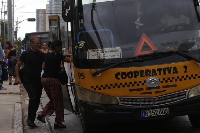 Un hombre y una mujer suben a un microbús en la capital de Cuba, operado por una de las cooperativas que gestionan el transporte en algunos importantes trayectos en La Habana, mientras detrás espera llegar a la parada uno de los nuevos autobuses que palian el déficit crónico del transporte público en el país. Crédito: Jorge Luis Baños/IPS
