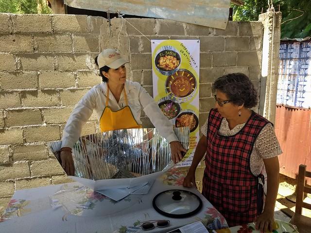Lorena Harp (I), responsable de promover las cocinas solares en México, muestra cómo armar el dispositivo a la maestra jubilada Irma Jiménez, en el barrio popular de Vicente Guerrero, en el municipio de Villa de Zaachila, en el sureño estado de Oaxaca. Crédito: Emilio Godoy/IPS