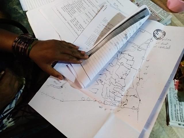 Una mujer muestra una solicitud para que se le reconozca su derecho a la propiedad de la tierra, en la aldea de Korchi, a 750 kilómetros al este de Mumbai, la capital económica de India. Un largo y dificultoso proceso que incluye mapas, pagos de impuestos de la familia por el terreno de al menos tres generaciones, entre los muchos documentos y firmas de familiares, el jefe de la aldea y funcionarios distritales, estadales y nacionales del departamento de Tierras, así como varias verificaciones posteriores. Crédito: Stella Paul / IPS