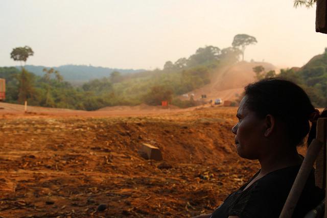 Una campesina observa la reconstrucción de una carretera amazónica en el estado de Pará, en el norte de Brasil. Larguísimas carreteras de sur a norte y de este a oeste fueron construidas durante la dictadura militar con el objetivo estratégico de integrar la ecorregión al resto del país, pero quedaron inconclusas o abandonadas y buena parte intransitables durante la estación de lluvias, hasta que se convirtieron en indispensables para la expansión agrícola. Crédito: Fabiana Frayssinet/IPS