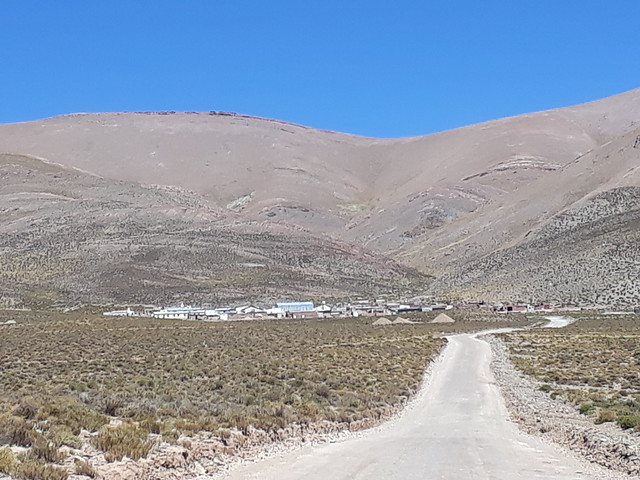 Al fondo, el pueblo de Olaroz, a 4000 metros de altura, con los cerros de la precordillera a sus espaldas. Frente al pueblo de la Puna argentina, está el salar del mismo nombre, en donde empresas extranjeras extraen litio. Sin embargo, las baterías de litio que hoy almacenan la energía solar del pueblo son importadas. Crédito: Daniel Gutman/IPS