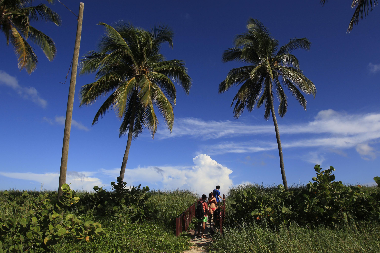 Un grupo de personas camina por una pasarela construida con el fin de proteger la duna de arena en el Consejo Popular de Guanabo, en el capitalino municipio Habana del Este, La Habana, Cuba.29 de octubre de 2019. Crédito: Jorge Luis Baños/IPS