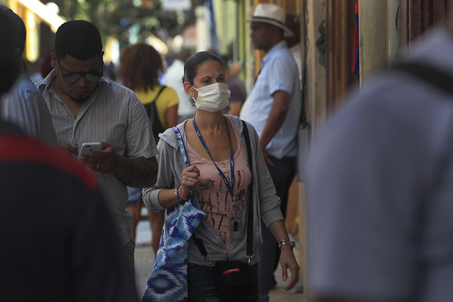 Una mujer camina por una calle del casco histórico de La Habana con una mascarilla protectora para prevenir el contagio del coranovirus. Foto: Jorge Luis Baños/IPS