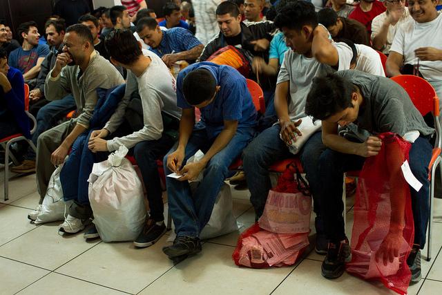Un grupo de deportados desde Estados Unidos en un centro de atención en San Salvador, antes de comenzar la emergencia por la pandemia de la covid-19, con las pocas pertenencias con que retornan al país. El aeropuerto internacional del país está cerrado salvo para los vuelos con migrantes retornados desde ese país y México. Foto: Edgardo Ayala/IPS
