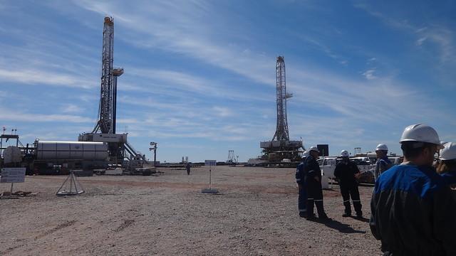 Unos técnicos dialogan cerca de dos torres de perforación en el yacimiento de petróleo y gas no convencional de Loma Campana, en Vaca Muerta, en Argentina. Foto: Fabiana Frayssinet/IPS