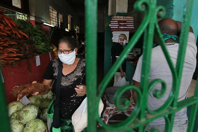 Una mujer, con una mascarilla de protección, abandona un mercado agropecuario con los productos frescos recién adquiridos, en un barrio de La Habana, en Cuba. Foto: Jorge Luis Baños/IPS