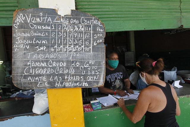 Un empleado despacha a una clienta productos racionados a precios subsidiados, incluidos en la libreta de abastecimiento cubana, en una desvencijada bodega del municipio de Playa, en La Habana. Foto: Jorge Luis Baños/IPS