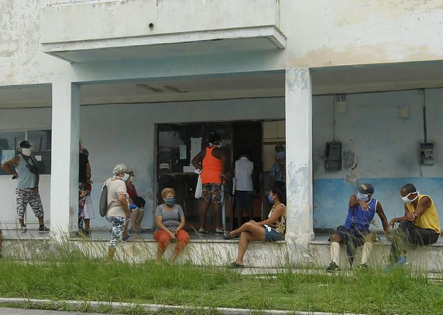Clientes mantienen la distancia y usan mascarillas protectoras para prevenir el contagio de la enfermedad covid-19 mientras aguardan en el exterior de una farmacia para adquirir medicamentos, en el municipio de 10 de Octubre de La Habana, en Cuba. Foto: Jorge Luis Baños/IPS