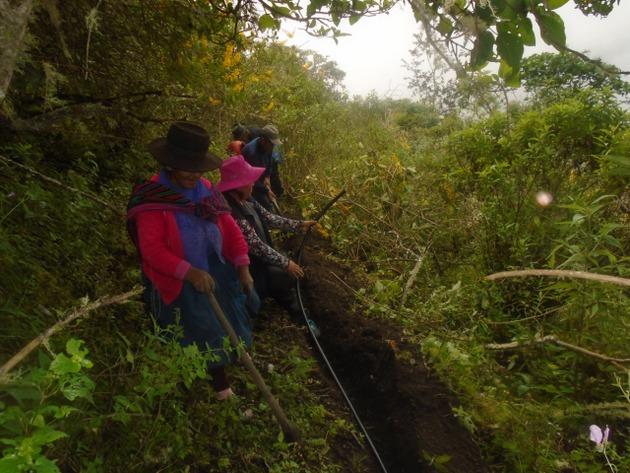 Mujeres y hombres trabajan en forma comunal en la conducción del agua con mangueras para el riego de sus sembradíos por el sistema de aspersión, y también para consumo humano, en el poblado de Oroncoy, en el altiplano de los Andes peruanos, integrado por unas 60 familias. Foto: Cortesía de Huñuc Mayu