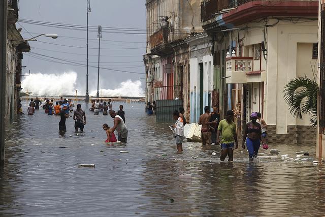 Residentes de La Habana transitan por una calle, transversal al malecón de la capital de Cuba, inundada por la embestida del mar tras el paso del huracán Irma, en septiembre de 2017. Foto: Jorge Luis Baños/IPS