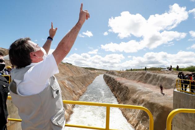 Un teatral Jair Bolsonaro clama al cielo en la inauguración de un tramo del canal de trasvase del río São Francisco para suministrar agua a cuatro estados de la región del Nordeste de Brasil, en la que perdió en las elecciones de 2018 y ahora pasó a prodigarse. La gigantesca obra de 700 kilómetros de canales, embalses y cauces fluviales está en construcción desde 2007 y aún no se concluyó. Foto: Alan Santos /PR