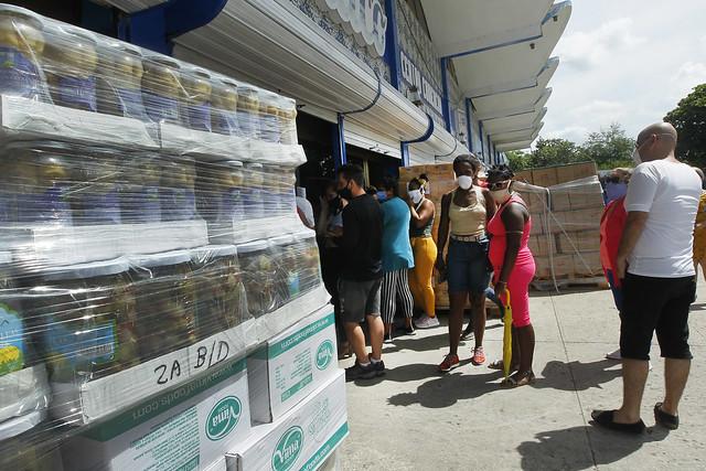Clientes en el exterior de un mercado que expende alimentos en moneda libremente convertible, en el municipio de Playa, en La Habana. Desde 2019, como parte de una estrategia para captar divisas, el gobierno de Cuba apostó por la apertura de estos establecimientos a los que solo acceden quienes reciben remesas en una decena de monedas extranjeras, depositadas en tarjetas habilitadas para la compra. Foto: Jorge Luis Baños/IPS