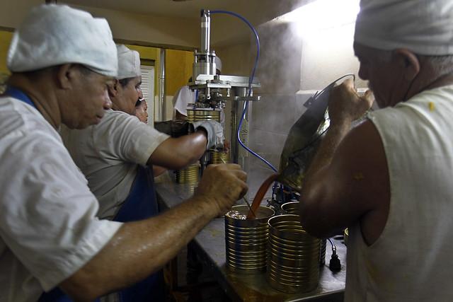 Trabajadores procesan frutas en la fábrica de conservas La Primada de la ciudad de Baracoa, en la oriental provincia cubana de Guantánamo. El reordenamiento monetario tendrá consecuencias profundas para los emprendimientos privados en un contexto inédito. Foto: Jorge Luis Baños/IPS