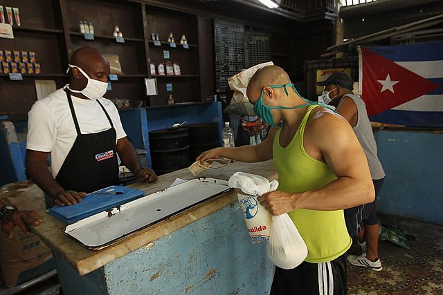 Un cliente paga unos productos racionados que se expenden a través de la libreta de abastecimiento en una bodega del municipio Playa, en La Habana. El aumento de los salarios y pensiones eliminará en Cuba los precios subsidiados de la cuota básica de alimentos y otros productos que el Estado oferta cada mes a los 11,2 millones de cubanos, mediante una cartilla de racionamiento instituida en 1962. Foto: Jorge Luis Baños/IPS