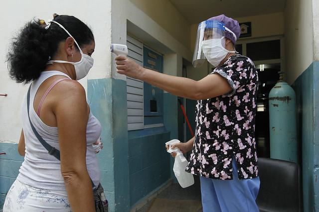 Una enfermera toma la temperatura a una mujer que acude a un policlínico en el municipio de Diez de Octubre, en La Habana. Cuba transita por la peor etapa de la epidemia de covid con un peligroso aumento de casos en las últimas semanas, ante lo cual las autoridades sanitarias fortalecen los protocolos y retoman medidas de aislamiento en varias de las 15 provincias y168 municipios del país. Foto: Jorge Luis Baños/IPS