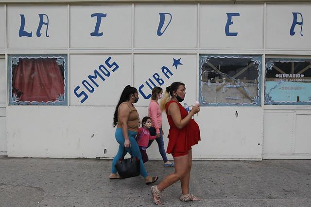 """Tres mujeres y una niña transitan, protegidas por sus mascarillas, por una calle de La Habana, junto a un cartel donde se lee: """"Somos Cuba"""". Pese a ser un país pequeño y con recursos financieros limitados, la industria biofarmacéutica tiene un alto desarrollo en Cuba y representa una importante fuente de ingresos para el Estado. Foto: Jorge Luis Baños/IPS"""