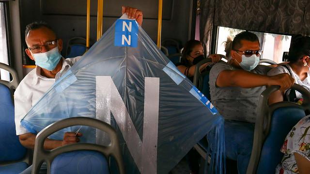 Francisco Reyes, de 61 años, vuelve a su casa en un autobús colectivo, luego de votar por el llamado bukelismo, como lo evidencia la cometa que lleva consigo, con los colores de azul cian del del partido del presidente Nayib Bukele y su partido, Nuevas Ideas. Foto: Edgardo Ayala / IPS