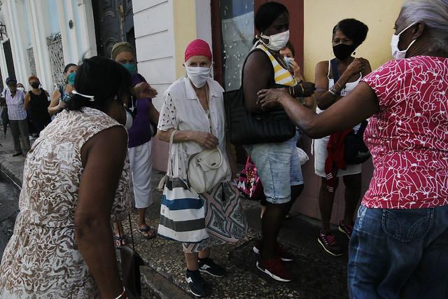 Adultos mayores, todos con mascarillas protectoras, aguardan en el exterior de una farmacia para la compra de medicamentos en medio de las restricciones impuestas para contener la expansión de la covid-19, en el municipio de Centro Habana, en la capital cubana. Iniciativas de acompañamiento a distancia buscan aportar apoyo psicosocial a segmentos de la envejecida población cubana. Foto: Jorge Luis Baños/IPS
