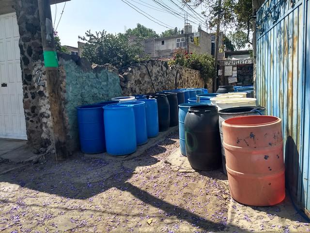 Los recipientes para almacenar el agua son parte del paisaje en las calles de Tehuixtitla. Los residentes de este barrio del sur de Ciudad de México los atesoran al lado de sus viviendas para complementar con ellos el suministro del recurso, mediante la compra de agua a los camiones cisterna, que guardan en bidones, algunos descoloridos por el sol y otros nuevos, para luego bombearla a sus viviendas. Foto: Emilio Godoy /IPS