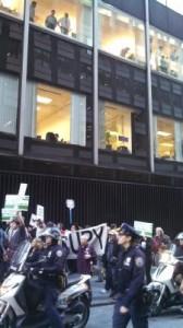 Banqueros observan a manifestantes del movimiento Robin Hood Tax que marchan por Nueva York el 17 de septiembre de 2013. Crédito: Samuel Oakford/IPS.