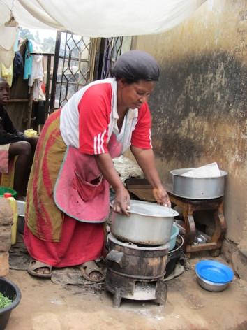 Una mujer en el tugurio ugandés de Katwe usa una cocina mejorada y eficiente para reducir el uso de carbón. Estos artefactos se distribuyen en Uganda como parte de proyectos para la reducción de emisiones. Crédito: Wambi Michael/IPS.