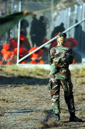 Una soldado observa a prisioneros de Guantánamo el 11 de enero de 2002. Crédito: Dominio público