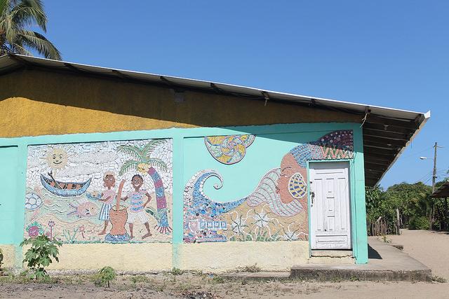 El mural de elementos reciclados, con que los pobladores de Santa Rosa de Aguán plasmaron su forma de vida y la belleza de la mujer garífuna, en una pared del centro comunal. Crédito: Thelma Mejía/IPS