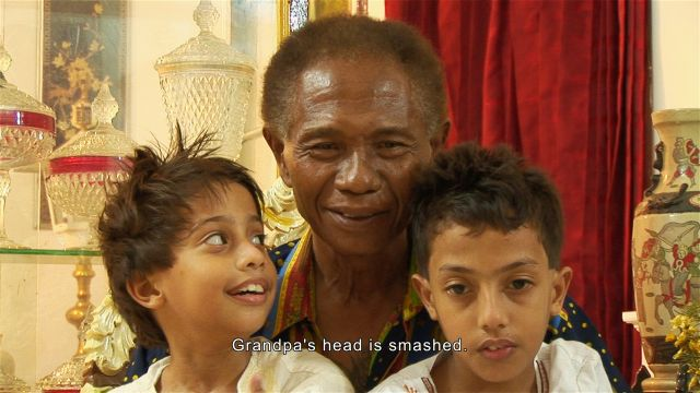 Anwar Congo mira el filme junto a sus nietos. Crédito: Cortesía de Joshua Oppenheimer