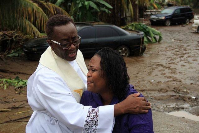 Un sacerdote reza con Colleen James en Cane Grove, San Vicente, horas antes de confirmarse que la hermana de la mujer había fallecido en las inundaciones. Su hija de dos años también está desaparecida. Crédito: Desmond Brown/IPS