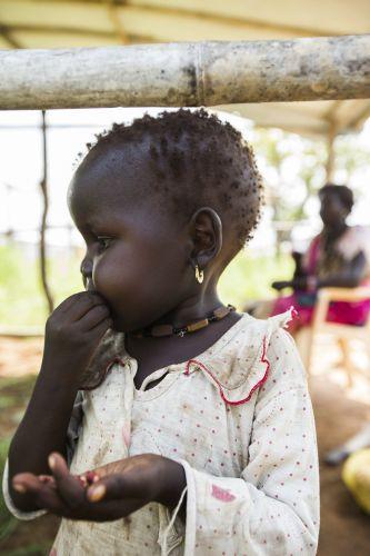 Una niña come un bocadillo en el nuevo refugio de su familia, en el campamento Protección de los Civiles III, cerca de Casa de la ONU, en Yuba,  la capital de Sudán del Sur. Crédito: UN Photo/JC McIlwaine