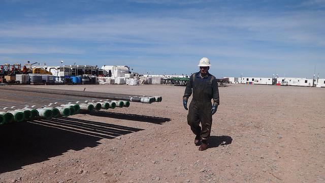 Un trabajador camina cerca de los tubos con los que se extrae el petróleo y el gas de esquisto en el campo de YPF en Loma Campana, en la sureña provincia argentina de Neuquén. Al fondo los contenedores que sirven de oficinas provisionales. Crédito: Fabiana Frayssinet /IPS