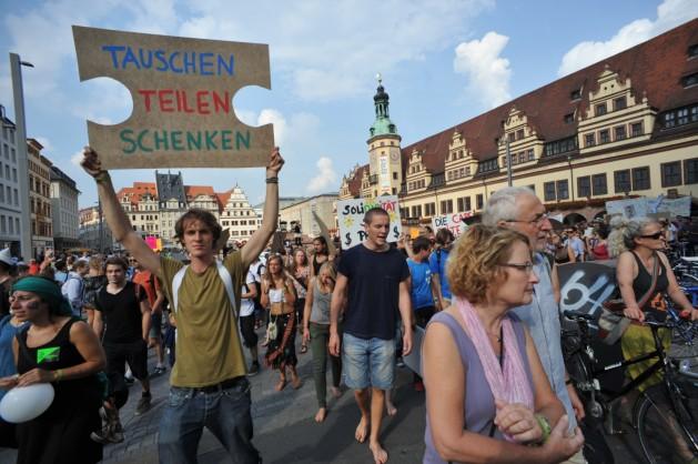 Manifestantes del decrecimiento en una marcha por las calles de Leipzig, en septiembre. El cartel dice: intercambia, comparte, da. Crédito: Klimagerechtigkeit Leipzig (http://klimagerechtigkeit.blogsport.de/)