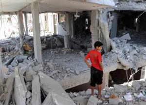 Un niño palestino observa los restos de un edificio destruido por un bombardeo en el campo de refugiados de Bureij Central, en la Franja de Gaza, en julio. Crédito: Shareef Sarhan/Archivos de UNRWA