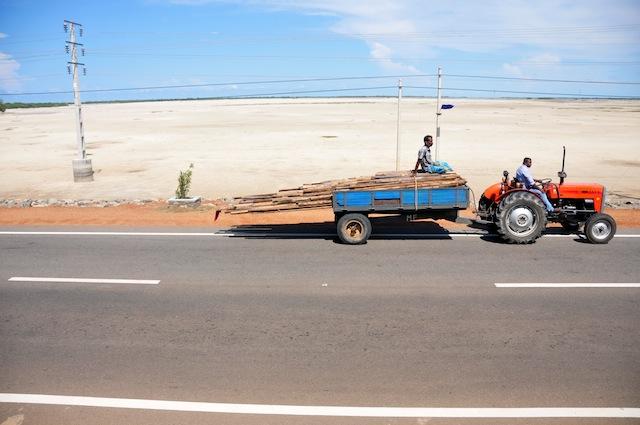 Un tractor avanza por la calzada seca al costado de una carretera sobre un terraplén en el  norteño distrito de Kilinochchi. Funcionarios consultados por IPS dijeron que la zona necesita nueve millones de rupias (unos 69.000 dólares) por semana de asistencia a causa de la sequía. Crédito: Amantha Perera/IPS.