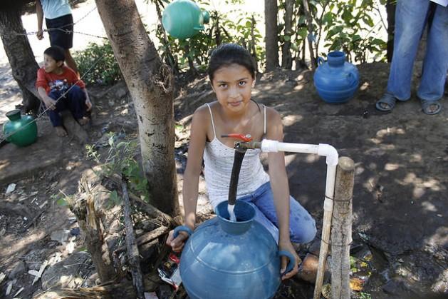 Jeniffer Hernández, de 12 años, llena su cántaro de agua de la toma colectiva en la comunidad de Los Pinos, en el municipio de Tacuba, en el occidente de El Salvador. Este es uno de los puntos donde quienes carecen de conexión por tubería a sus hogares, acceden gratuitamente al recurso. Crédito: Edgardo Ayala/IPS