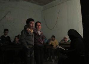 Dos niños cantan abrazados en una escuela subterránea de la ciudad siria de Alepo, octubre de 2014. Crédito: Shelly Kittleson/IPS.