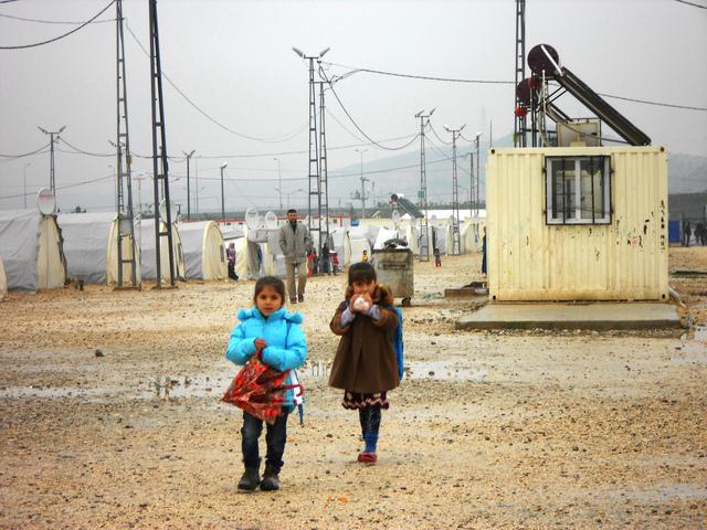 En una fría mañana, dos niñas caminan hacia la escuela entre las tiendas de campaña del campo de refugiados sirios de Nizip, en Turquía. Crédito: Fabíola Ortiz/IPS
