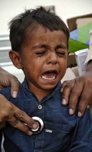 Un niño llora mientras se somete a un chequeo médico en un hospital improvisado. Los expertos dicen que los centros sanitarios en Tharparkar dejan mucho que desear. Crédito: Irfan Ahmed/IPS