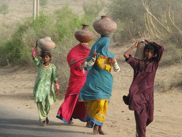 Muchas mujeres viajan durante horas para llegar a los pozos y retornar a sus casas con el agua, todos los días. Crédito: Irfan Ahmed/IPS