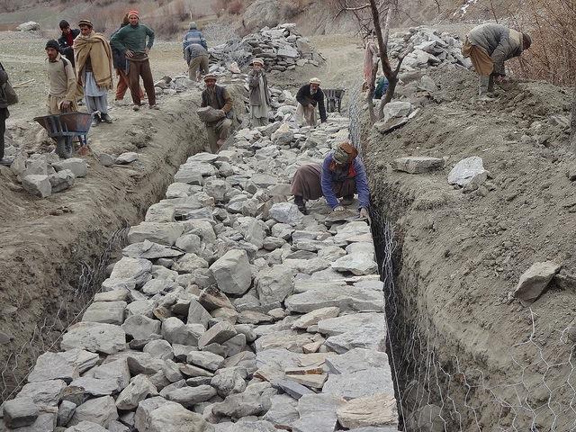 Obreros construyen muros de contención para controlar inundaciones en el norteño valle pakistaní de Bindo Gol. Crédito: Saleem Shaikh/IPS