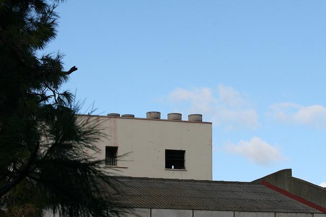El amianto está prohibido en España desde 2002, pero su uso es visible aún en muchas formas, como en un ondulado tejado de fibrocemento o en los cilíndricos depósitos de agua sobre la azotea del edificio colindante, cerca de la céntrica Plaza de la Merced, en la ciudad de Málaga. Crédito: Inés Benítez/IPS