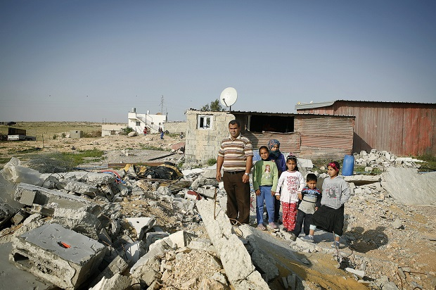 """Naif Agele con sus hijos y sobrinos en las ruinas de la casa de su hermano, en una zona """"no reconocida"""" de la localidad de Kuseife, en el desierto de Néguev. La vivienda fue demolida por las autoridades israelíes el 10 de marzo de 2014. Crédito: Silvia Boarini / IPS"""