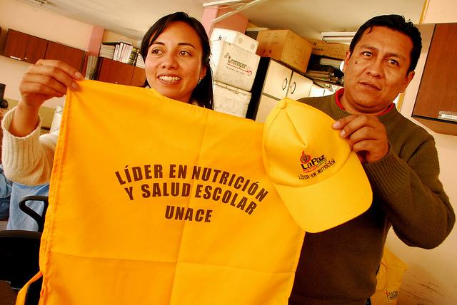 Profesionales de la Unidad de Alimentación Complementaria Escolar de la alcaldía de La Paz muestran el uniforme que van a portar los escolares que capacitan para que sean líderes en nutrición y salud escolar en los centros educativos del municipio. Crédito: Franz Chávez/IPS