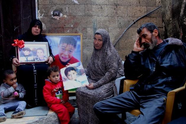 Sahar Baker (izquierda), con Ahed Baker (derecha) y su cuñada, con fotos de los cuatro primos muertos por la artillería israelí en 2014 mientras jugaban al fútbol en la playa de Gaza. Crédito: Khaled Alashqar/IPS