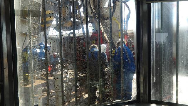 Técnicos de YPF laboran en la base de una de las torres perforadoras de petróleo de esquisto, en el yacimiento de Loma Campana, en Vaca Muerta, en el suroeste de Argentina. Crédito: Fabiana Frayssinet/IPS