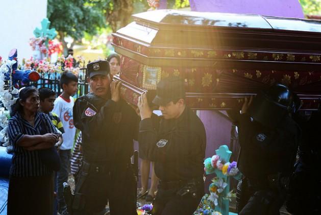 Familiares, vecinos y efectivos de la Policía Nacional Civil durante el entierro del agente Justo Germán Gil, de la Unidad de Mantenimiento del Orden, muerto por pandilleros en el municipio de San Juan Opico, en el este de El Salvador, el 10 de enero de 2015. Crédito: Vladimir Girón/IPS
