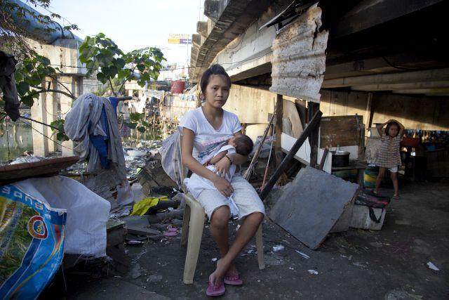 Rizelle, de 17 años, y su bebé de tres semanas, viven debajo de un puente en San Dionisio, Indonesia. Crédito: Save the Children